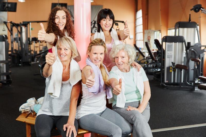 Mulheres novas e superiores que mantêm os polegares foto de stock