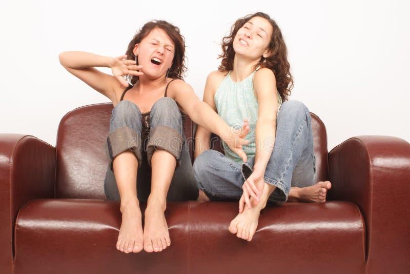 Mulheres Novas Que Sentam-se No Revestimento Do Sofá Que Presta Atenção à Tevê Fotos de Stock