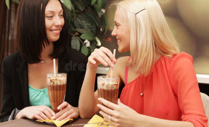 Mulheres novas que têm a ruptura de café junto fotografia de stock