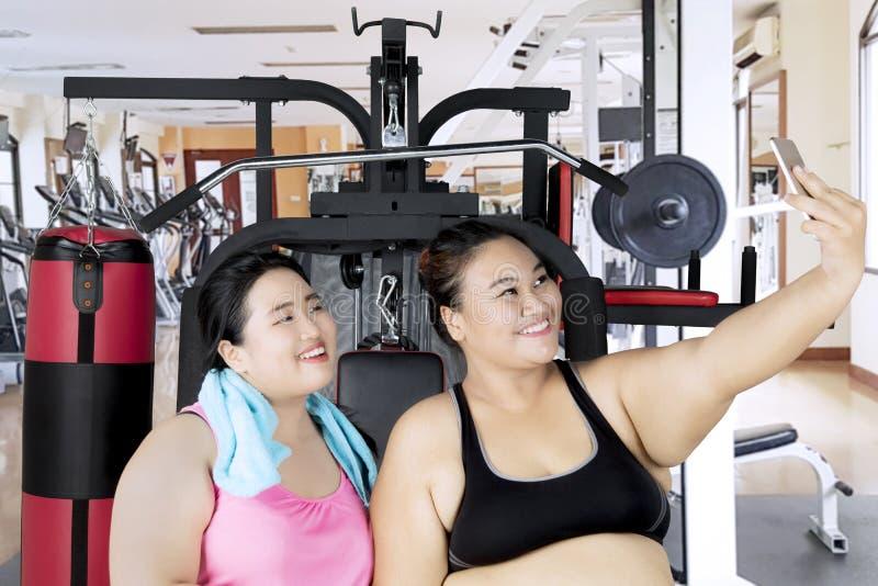 Mulheres obesos com o smartphone no centro do gym imagem de stock