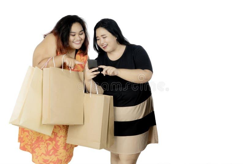 Mulheres obesos com smartphone e sacos de compras fotos de stock