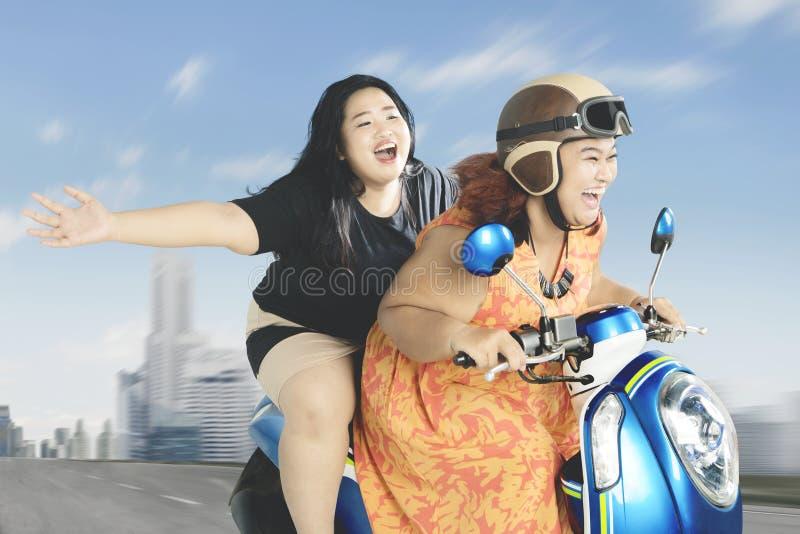 Mulheres obesos que apreciam sua viagem com 'trotinette' imagem de stock royalty free