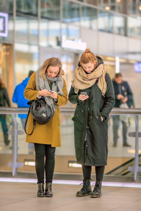 Mulheres ocupadas com telefone esperto em uma estação de trem, Utrecht, Países Baixos imagem de stock