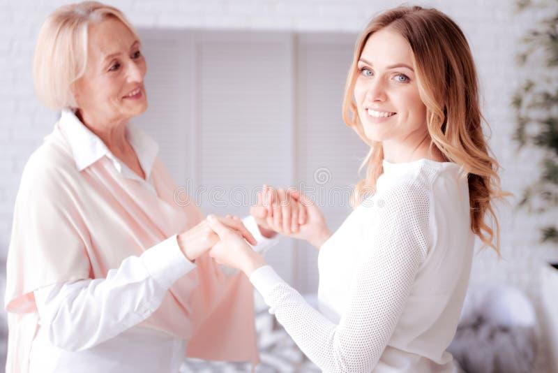 Mulheres positivas felizes que guardam as mãos imagens de stock