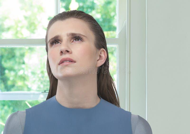 Mulheres preocupadas que olham acima para a esperança contra a janela ensolarada imagens de stock royalty free
