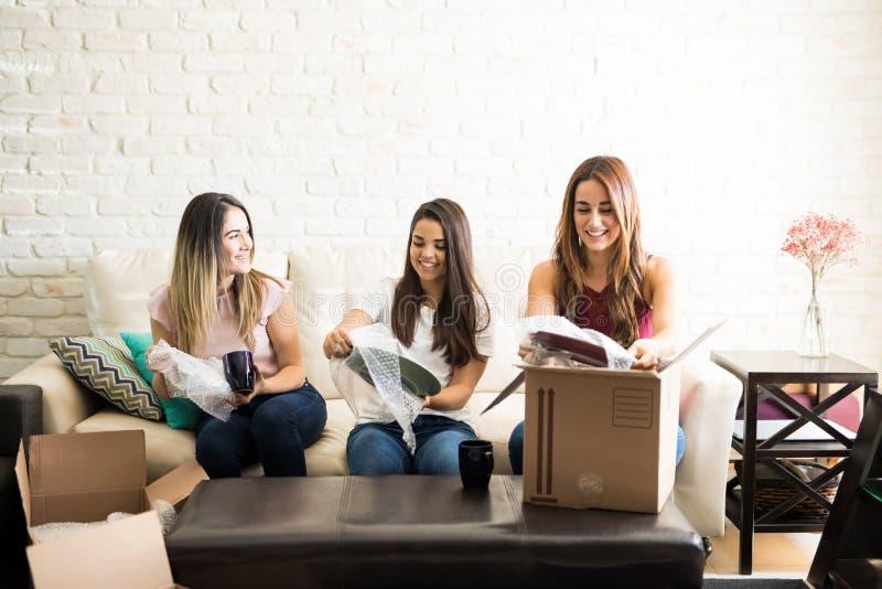 Mulheres que ajudam o amigo a embalar foto de stock royalty free
