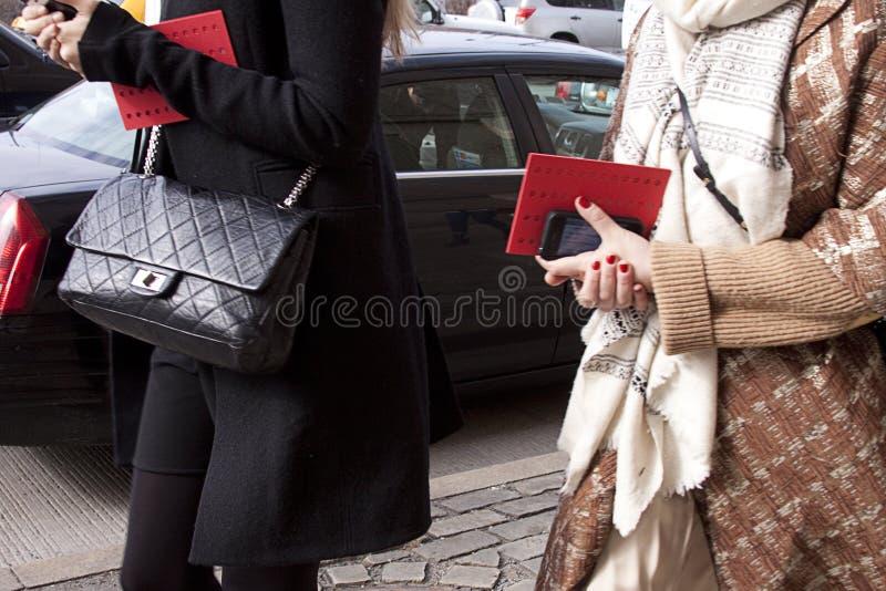 Mulheres que andam com bolsa do desenhista e que guardam o smartphone e o convite imagem de stock