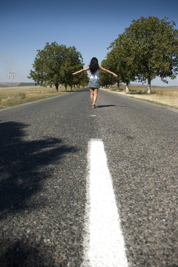 Mulheres que andam na estrada vazia no país imagens de stock royalty free