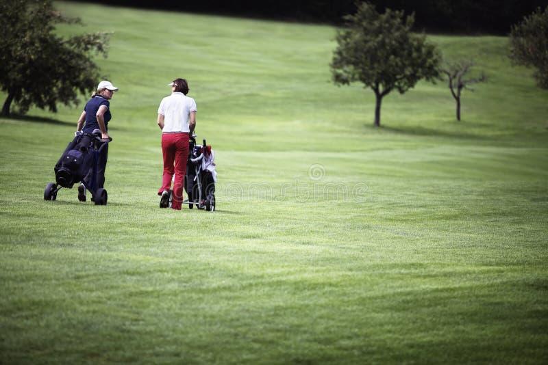 Mulheres que andam no campo de golfe com troles. imagem de stock royalty free