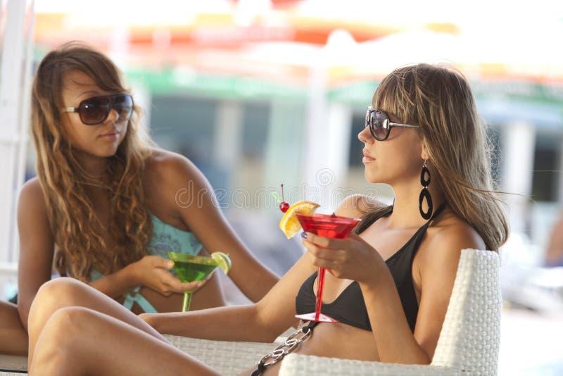 Mulheres que apreciam na barra com uns vidros de martini imagens de stock royalty free