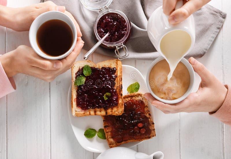 Mulheres que bebem o chá com leite e brindes deliciosos, vista superior imagem de stock royalty free