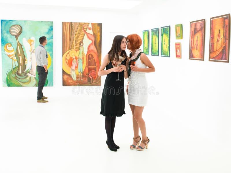 Mulheres que bisbilhotam na galeria de arte imagens de stock