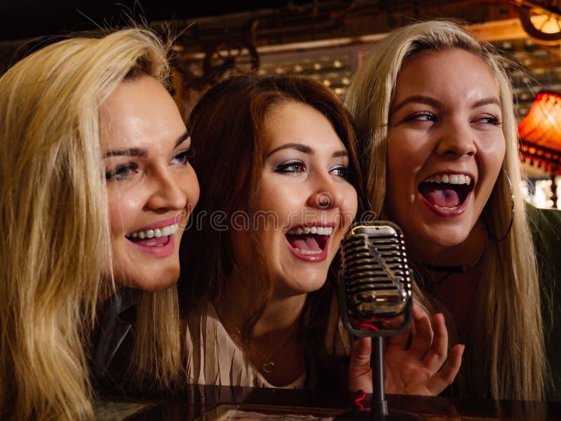 Mulheres que cantam com microfone imagens de stock