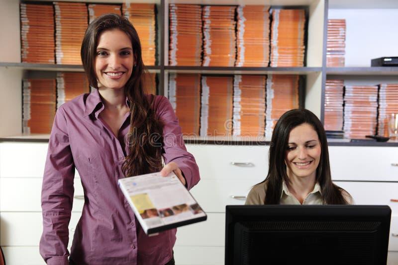 Mulheres que cedem o dvd na loja rental video imagens de stock