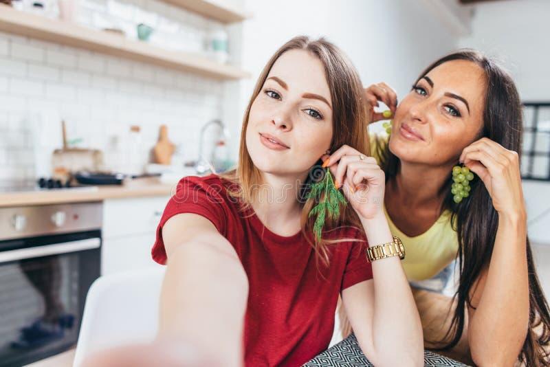 Mulheres que comem o café da manhã na cozinha que joga com alimento e que toma o selfie imagem de stock