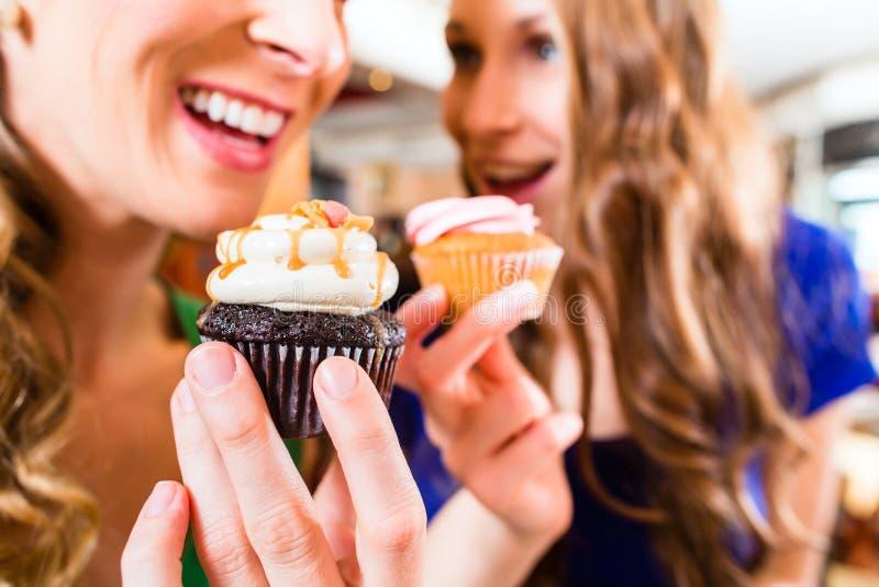 Mulheres que comem queques quando beber do café imagens de stock royalty free