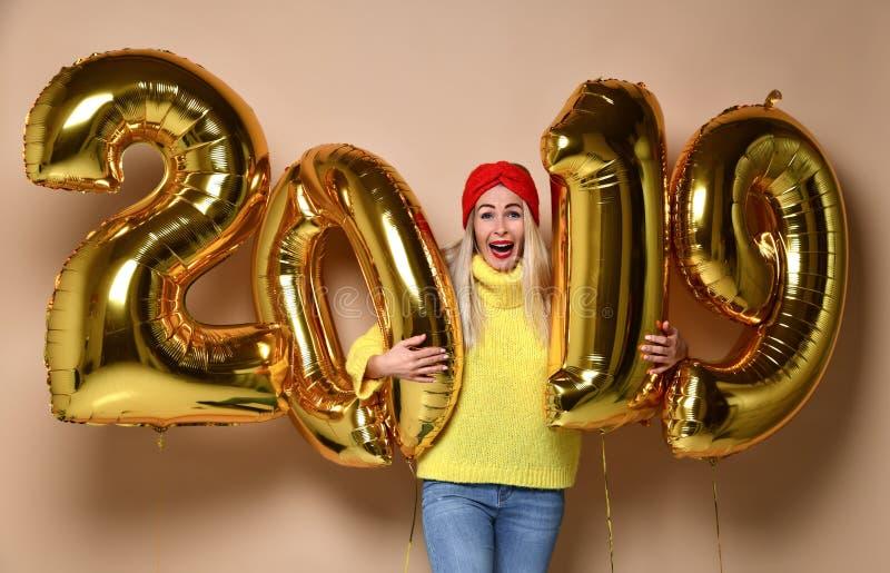 Mulheres que comemoram o riso feliz do partido do ano novo na blusa amarela da camiseta com os balões 2019 do ouro imagens de stock