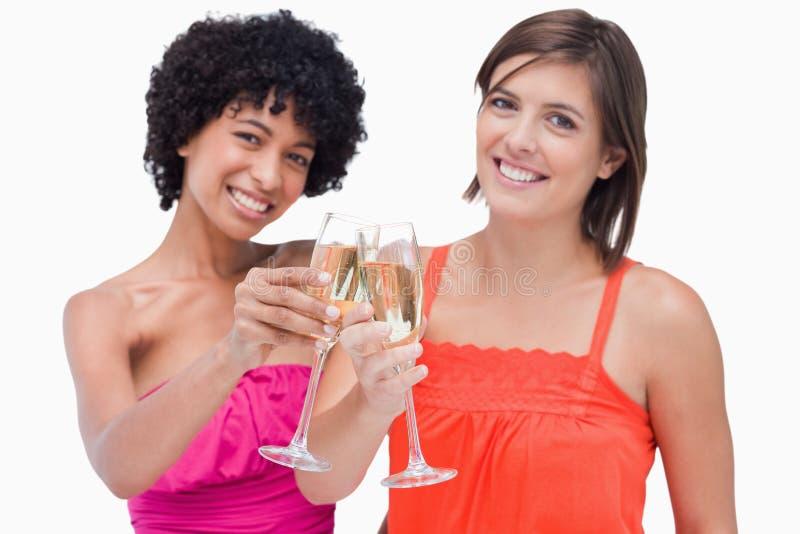 Mulheres que comemoram um evento clinking o champanhe imagens de stock