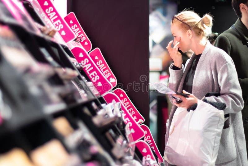 Mulheres que compram e que testam cosméticos em uma loja da beleza fotos de stock