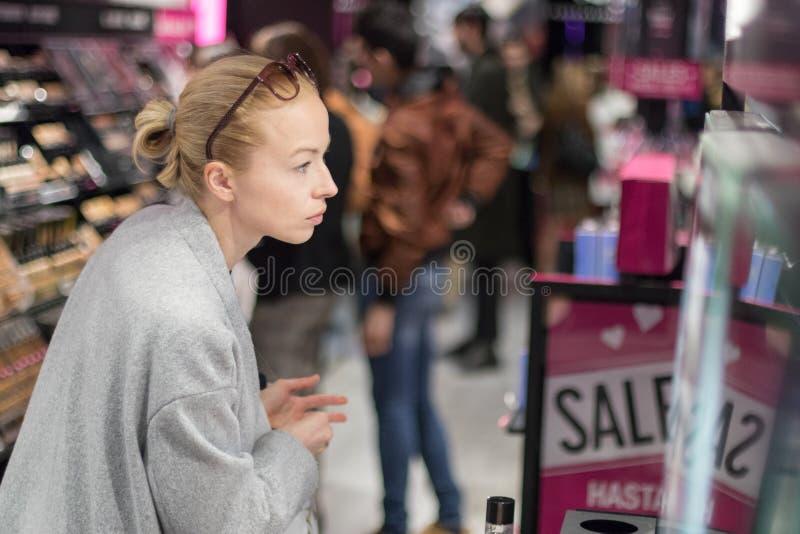 Mulheres que compram e que testam cosméticos em uma loja da beleza imagens de stock