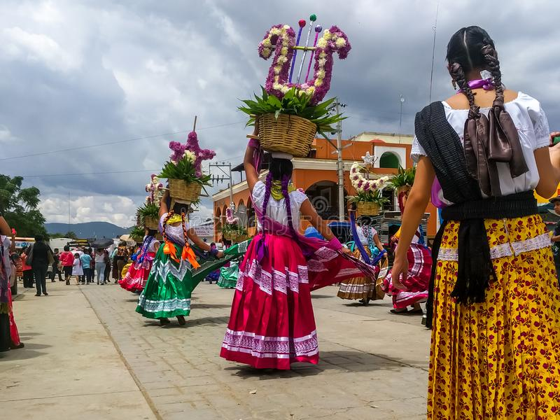 Mulheres que dançam através das ruas com ofertas na celebração de Guelaguetza imagem de stock