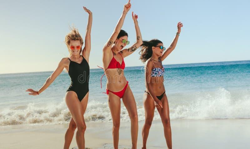 Mulheres que dançam na praia que levanta as mãos fotografia de stock royalty free