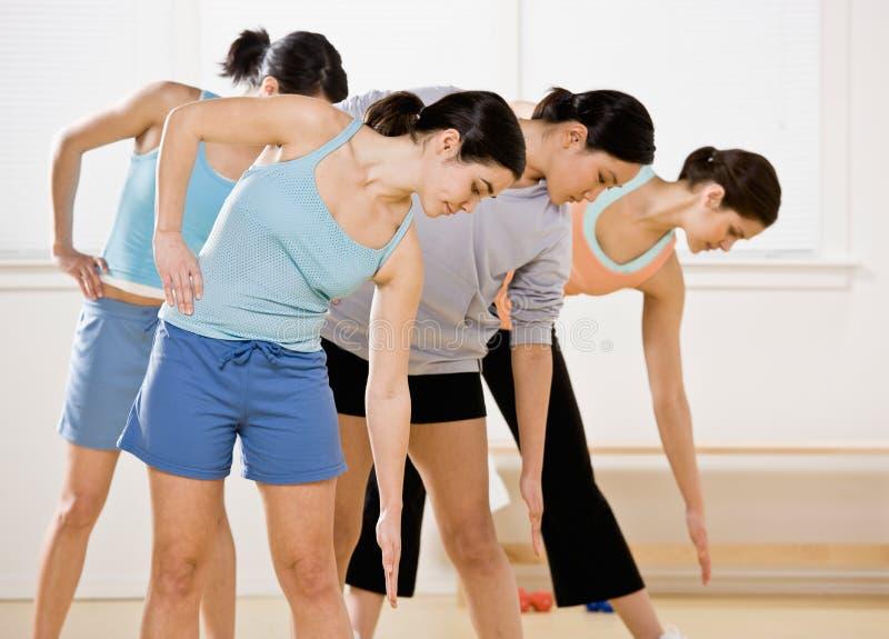 Mulheres que dobram-se e que esticam durante a classe imagem de stock royalty free