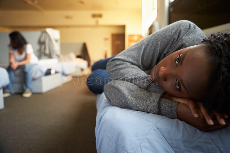 Mulheres que encontram-se em camas no abrigo desabrigado imagens de stock