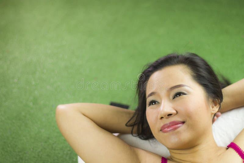 Mulheres que encontram-se na grama verde, em um sorriso bonito e levantando, mulher tailandesa que estabelece na grama verde fotografia de stock royalty free