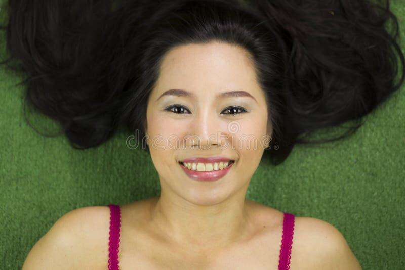 Mulheres que encontram-se na grama verde, em um sorriso engra?ado bonito e ativo, mulher tailandesa que estabelece na grama verde fotografia de stock royalty free