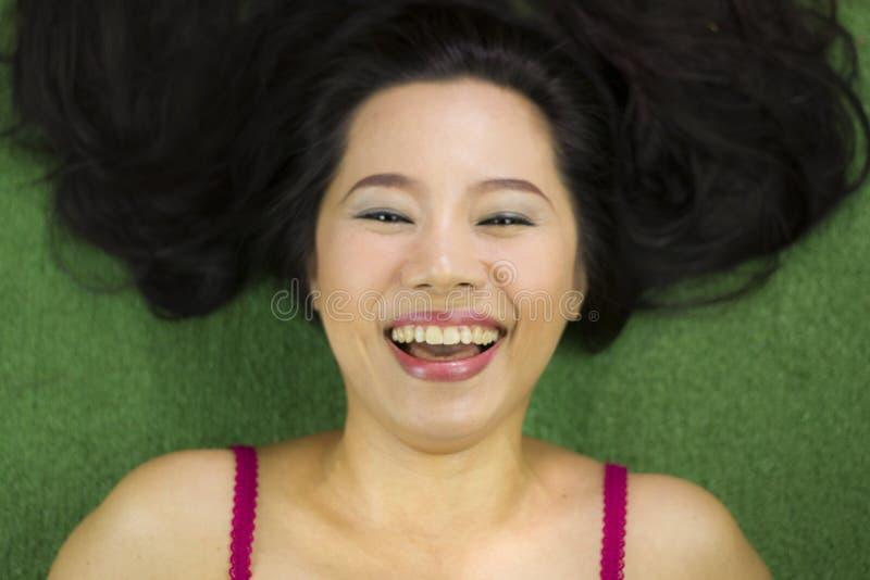Mulheres que encontram-se na grama verde, em um sorriso engra?ado bonito e ativo, mulher tailandesa que estabelece na grama verde imagens de stock