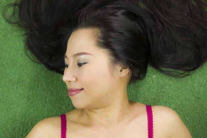 Mulheres que encontram-se na grama verde, em um sorriso engra?ado bonito e ativo, mulher tailandesa que estabelece na grama verde imagem de stock