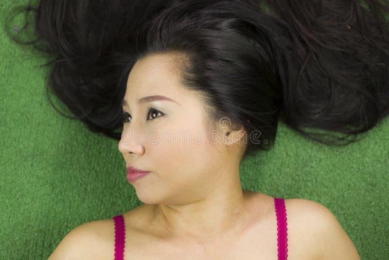 Mulheres que encontram-se na grama verde, em um sorriso engra?ado bonito e ativo, mulher tailandesa que estabelece na grama verde imagem de stock royalty free