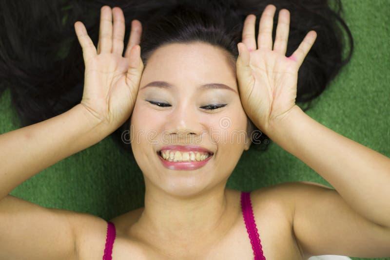 Mulheres que encontram-se na grama verde, em um sorriso engra?ado bonito e ativo, mulher tailandesa que estabelece na grama verde imagens de stock royalty free