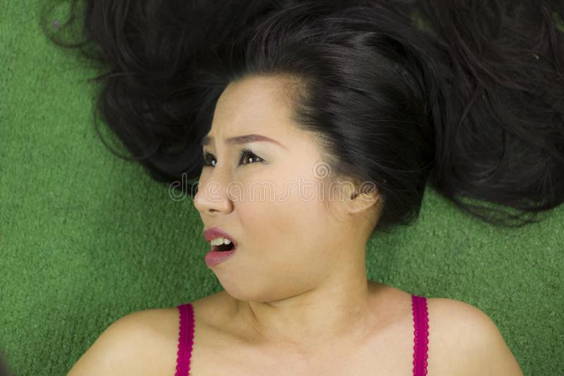 Mulheres que encontram-se na grama verde, em um sorriso engra?ado bonito e ativo, mulher tailandesa que estabelece na grama verde fotografia de stock