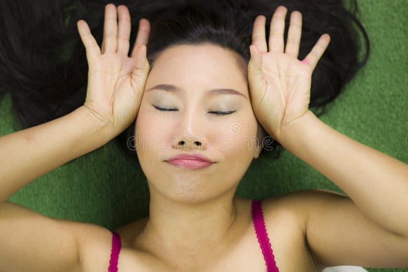 Mulheres que encontram-se na grama verde, em um sorriso engra?ado bonito e ativo, mulher tailandesa que estabelece na grama verde foto de stock