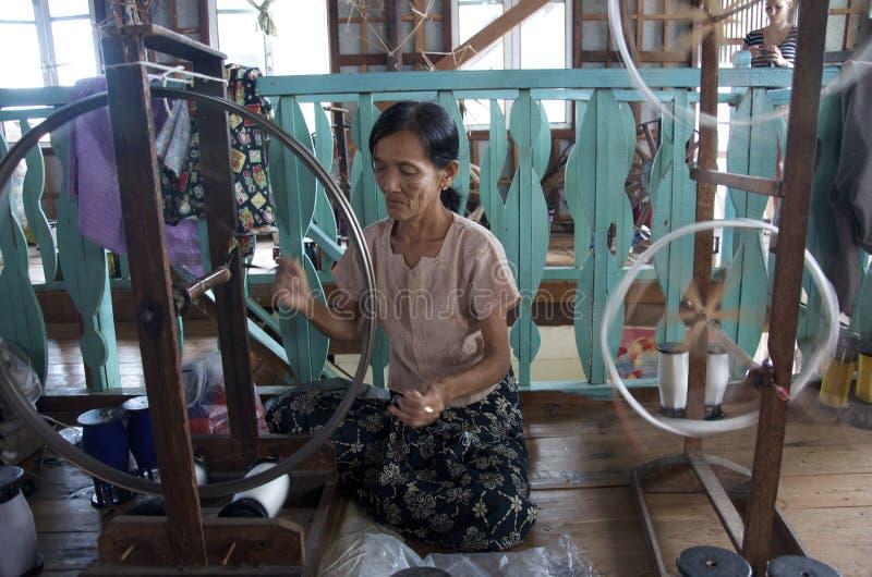 Mulheres que enrolam para fora a seda para obtê-la pronta para tecer foto de stock