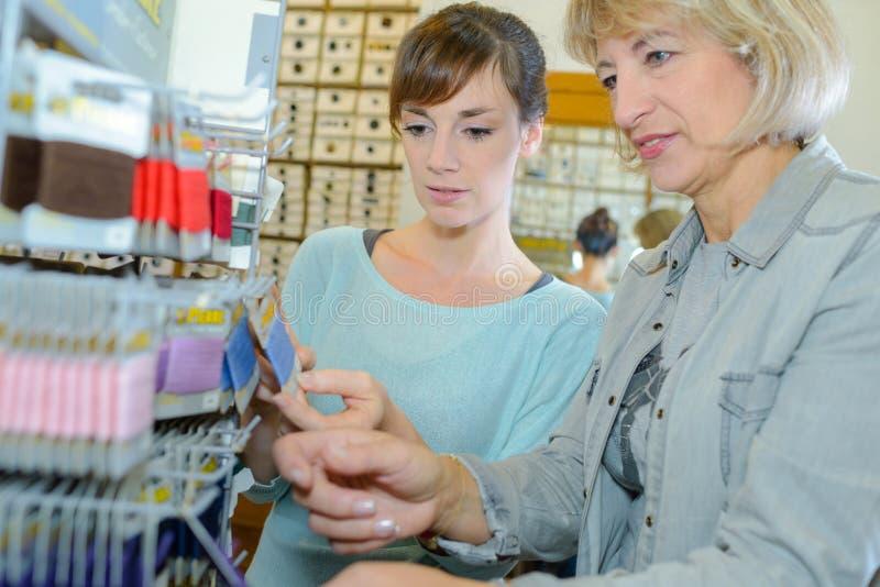 Mulheres que escolhem linhas nas miudezas foto de stock royalty free