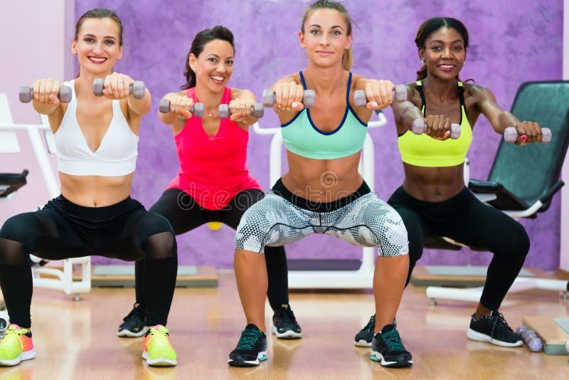 Mulheres que fazem as ocupas que guardam pesos no grou funcional do treinamento imagem de stock royalty free