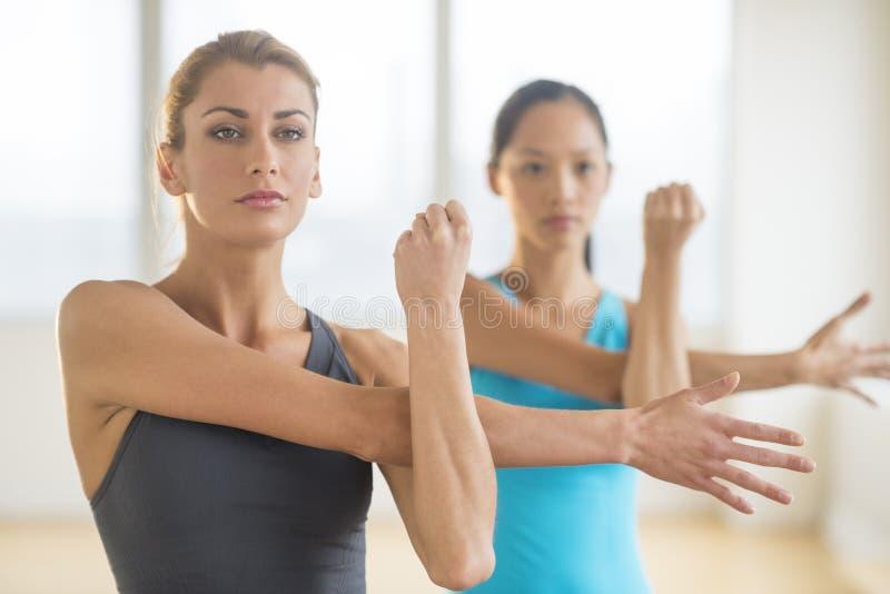 Mulheres que fazem esticando o exercício no Gym fotografia de stock royalty free