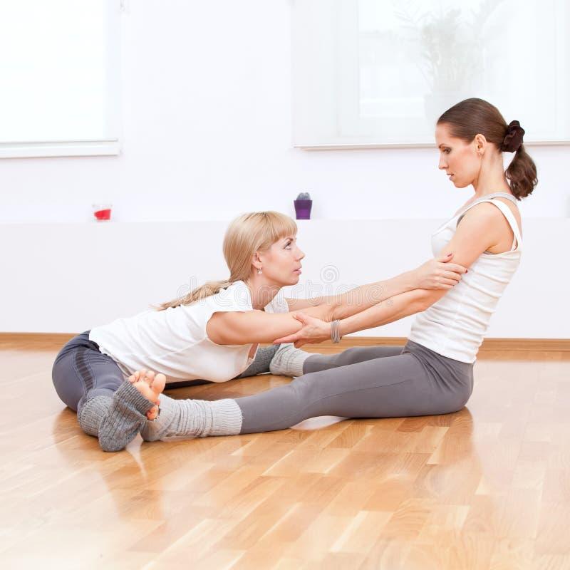 Mulheres que fazem o exercício da ioga na ginástica fotografia de stock royalty free