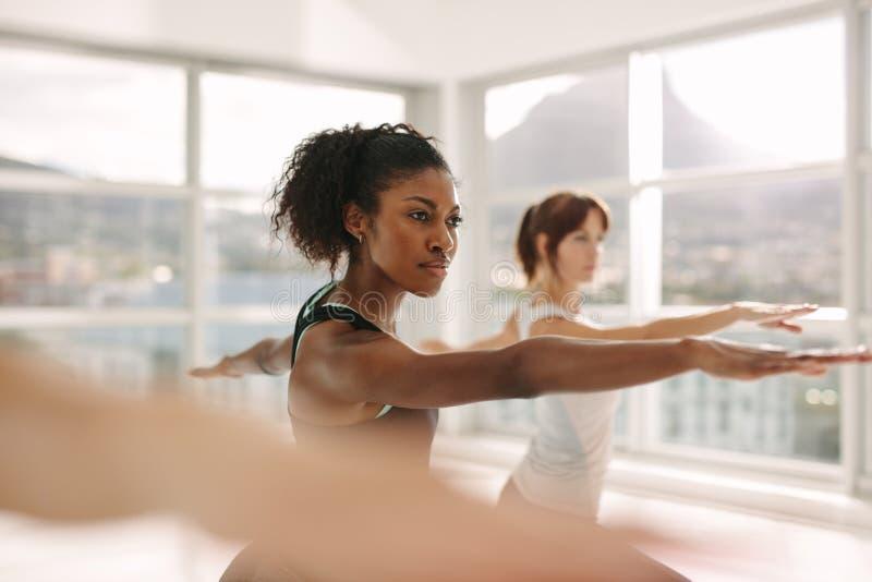 Mulheres que fazem o exercício do esticão e da ioga no gym fotografia de stock