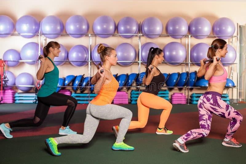 Mulheres que fazem um exercício de pé na classe de ginástica aeróbica imagem de stock royalty free