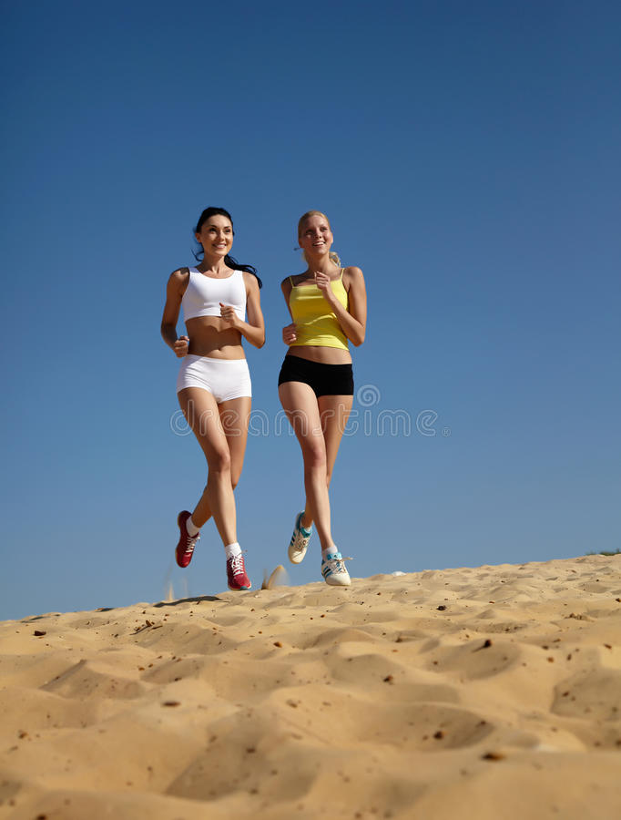 Mulheres que funcionam na praia imagens de stock royalty free