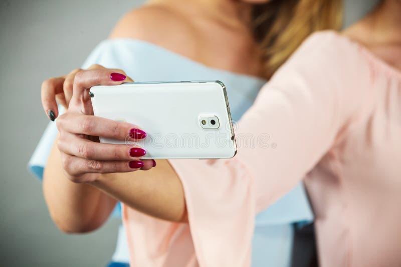 Mulheres que guardam o smartphone imagem de stock
