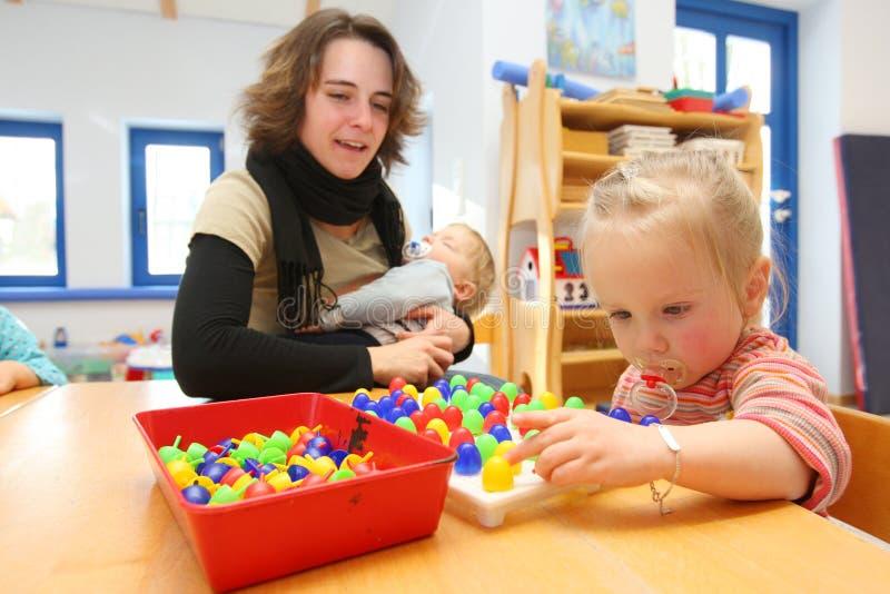 Mulheres que jogam com as crianças no centro de centro de dia fotografia de stock