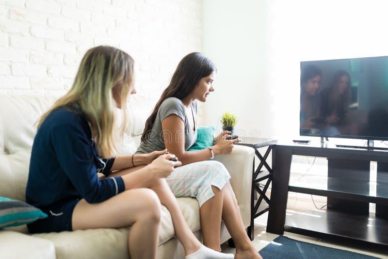 Mulheres que jogam o videogame durante o partido de pijama imagem de stock