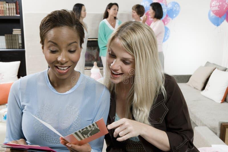 Mulheres que leem o cartão em uma festa do bebê foto de stock