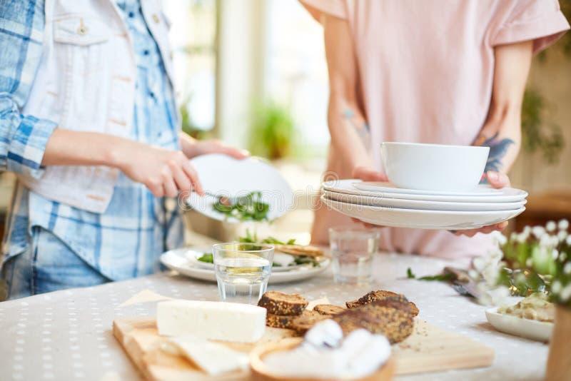 Mulheres que limpam a tabela após o jantar imagem de stock royalty free