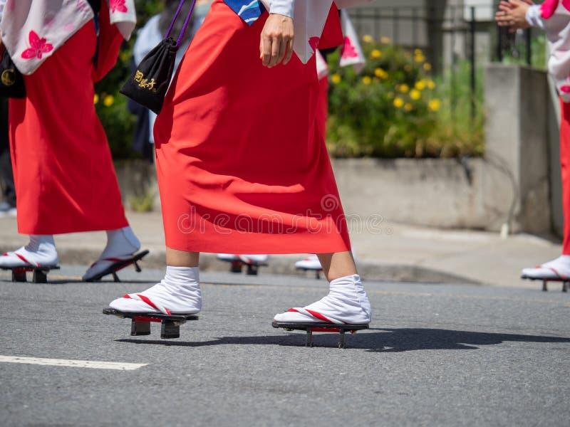Mulheres que marcham nas sandálias japonesas geta durante uma parada imagem de stock